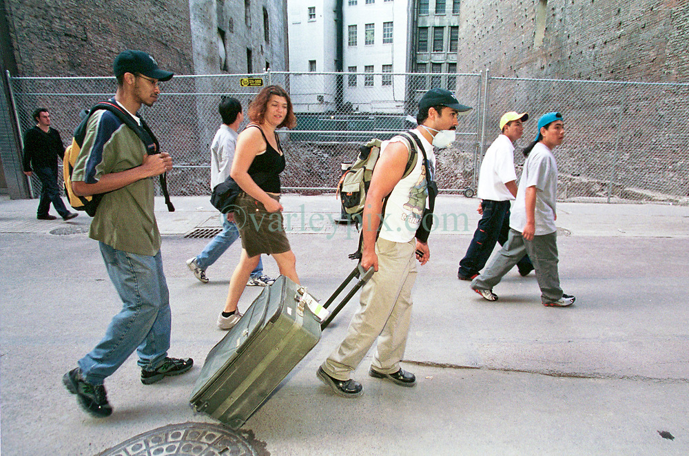 18 September 2001. New York, New York - USA.<br /> Post 9/11 World Trade Center attack.<br /> John Philips walks away from Wall Street, his belongings crammed into a suitcase as he becomes a refugee from his luxury apartment just 2 blocks from the site of the Twin Towers collapse. John was granted special permission to enter his once luxury apartment close to where the World Trade Center Twin Towers used to stand. His apartment is now filled with dust and debris from the collapsed towers. John and residents of the building were evacuated following the attack which cut off water and electricity supplies. A week after the attack, residents were given just 15 minutes to gather necessary belongings and leave their apartments which by default rendered them homeless, perhaps the first refugees of the War on Terror. Residents were warned to check their balconies for victims of the Twin Towers who might have fallen to their deaths.<br /> In the chaos of 9/11, John's sister Dr Sneha Ann Philip disappeared. John claimed she used to walk past the Twin Towers every morning on her way to work. He fears she might be a victim of the coordinated Al Qaeda attack which claimed over 2,000 victims at the site of the Twin Towers.<br /> It was later discovered that his sister was indeed just one more of the many victims killed in the attack.<br /> Photo exclusive©; Charlie Varley/varleypix.com