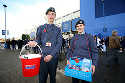 Members of armed forces collect money for poppies outside the stadium prior to the match
