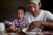 Pima farmer Jose Angel Galaviz Carrillo and his youngest son, Favien, mop up their breakfast bowls of fried pinto beans with pieces of tortillas made by his wife Estella at their home in Maycoba, Sonora, Mexico. (From the book What I Eat: Around the World in 80 Diets.) MODEL RELEASED.