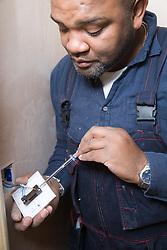 Electrician fixing an electric plug socket,