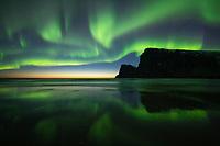 Spectacular Northern Lights - Aurora Borealis fill sky over Kvalvika beach and surrounding mountains, Lofotodden National Park, Moskenesøy, Lofoten Islands, Norway
