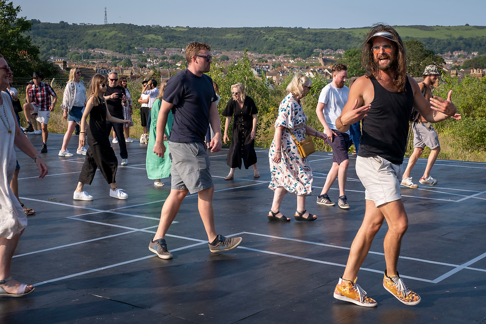 People gathered to dance on Beautiful Sunday, a sculptural installation by the artist Jacqueline Donachie that celebrates 'all the dance floors of Folkestone' by marking out their size one-to-one on a huge stage set in the middle of the derelict gasworks site. Visitors are invited to stand on the stage and remember (if they are local residents) the dance floors - many of which are no longer active on the 21st of July 2021, in Folkestone, United Kingdom. The artwork is part of the Creative Folkestone Triennial 2020, The Plot, which sees 27 newly commissioned artworks appearing around the south coast seaside town. The new work builds on the work from previous triennials making Folkestone the biggest urban outdoor contemporary art exhibition in the UK. (photo by Andrew Aitchison / In pictures via Getty Images)