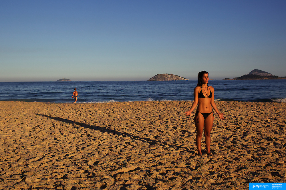 A beach goer meditates in the late afternoon sunshine on Ipanema beach, Rio de Janeiro,  Brazil. 6th July 2010. Photo Tim Clayton..The beaches of Rio de Janeiro, provide the ultimate playground for locals and tourists alike. Beach activity is in abundance as beach volley ball, football and a hybrid of the two, foot volley, are played day and night along the length and breadth of Rio's beaches. .Volleyball nets and football posts stretch along the cities coastline and are a hive of activity particularly at it's most famous beaches Copacabana and Ipanema. .The warm waters of the Atlantic Ocean provide the ideal conditions for a variety of water sports. Walkways along the edge of the beaches along with exercise stations and cycleways encourage sporting activity, even an outdoor gym is available at the Parque Do Arpoador overlooking the ocean. .On Sunday's the main roads along the beaches of Copacabana, Leblon and Ipanema are closed to traffic bringing out thousands of people of all ages to walk, run, jog, ride, skateboard and cycle more than 10 km of beachside roadway. .This sports mad city is about to become a worldwide sporting focus as they play host to the world's biggest sporting events with Brazil hosting the next Fifa World Cup in 2014 and Rio de Janeiro hosting the Olympic Games in 2016...