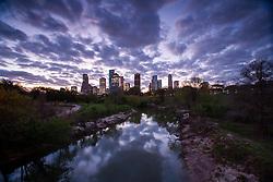 Beautiful sky with nimbus clouds reflected in Buffalo Bayou with Houston, Texas skyline at dusk.