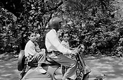 Father and 2 boys ride on motorcycle