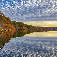 New England fall scenery reflecting in Olney Pond at Lincoln Woods State Park in Lincoln RI displaying the beautiful Rhode Island colors of autumn in all tones. <br />