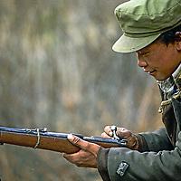 CHINA, TIBET, Tsangpo Gorge. A hunter (poacher) from Kykar village loads his venerable weapon to shoot takin or musk deer.