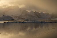 Incoming snowstorm conceals mountain peaks of Moskenesøy, Lofoten Islands, Norway