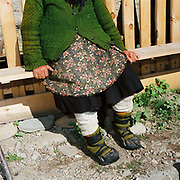 An elderly Romanian woman sits on a wooden bench outside her home, Botiza, Maramures, Romania. She's wearing a hand knitted green cardigan, a flowery apron, traditional footwear (opinci) and woollen socks (caltuni).