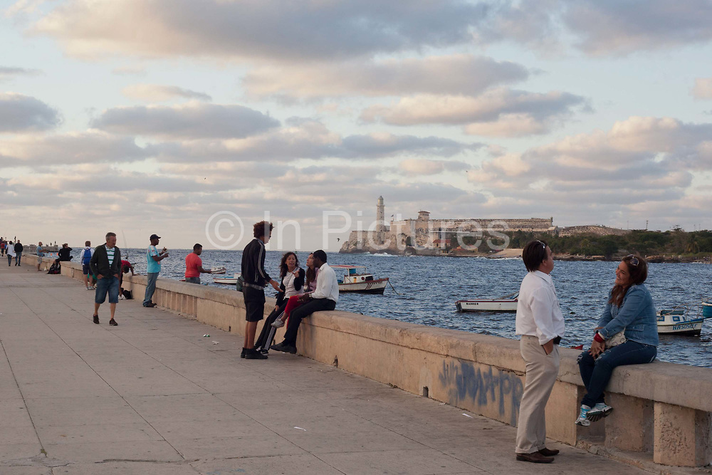Couples and people walk down the waterfront near the Malecon in Havana, overlooking the water and taking in the evening air.