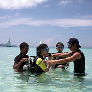 Asian tourists during a scuba diving lesson in the ocean at White Beach,  Boracay Island, the Philippines on October 3, 2008, Photo Tim Clayton.....Asian tourists at White Beach, Boracay Island, the Philippines...The 4 km stretch of White beach on Boracay Island, the Philippines has been honoured as the best leisure destination in Asia beating popular destinations such as Bali in Indonesia and Sanya in China in a recent survey conducted by an International Travel Magazine with 2.2 million viewers taking part in the online poll...Last year, close to 600,000 visitors visited Boracay with South Korea providing 128,909 visitors followed by Japan, 35,294, USA, 13,362 and China 12,720...A popular destination for South Korean divers and honeymooners, Boracay is now attracting crowds of tourists from mainland China who are arriving in ever increasing numbers. In Asia, China has already overtaken Japan to become the largest source of outland travelers...Boracay's main attraction is 4 km of pristine powder fine white sand and the crystal clear azure water making it a popular destination for Scuba diving with nearly 20 dive centers along White beach. The stretch of shady palm trees separate the beach from the line of hotels, restaurants, bars and cafes. It's pulsating nightlife with the friendly locals make it increasingly popular with the asian tourists...The Boracay sailing boats provide endless tourist entertainment, particularly during the amazing sunsets when the silhouetted sails provide picture postcard scenes along the shoreline...Boracay Island is situated an hours flight from Manila and it's close proximity to South Korea, China, Taiwan and Japan means it is a growing destination for Asian tourists... By 2010, the island of Boracay expects to have 1,000,000 visitors.