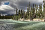 A patch of sun breaks through the clouds over a river near Jasper, Alberta, Canada