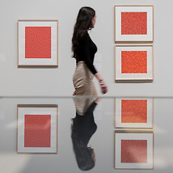 """© Licensed to London News Pictures. 09/10/2018. LONDON, UK. A visitor walks by screen prints and studies for """"Red Meander I"""", 1969-70 and """"TRI"""", 1969-70, by Anni Albers.  Preview of the UK's first exhibition of works by German artist Anni Albers at Tate Modern who used the ancient art of hand-weaving to produce works of modern art.  Over 350 of her artworks from major collections from Europe and the US are on show 11 October to 27 January 2019.  Photo credit: Stephen Chung/LNP"""