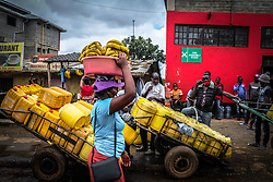 May 5, 2020, Nairobi, Kenya: A banana vendor walks past a  group of local water vendors waiting in line to fill their cans during the scarcity of water amidst the ongoing Curfew due to the corona virus pandemic..Across most neighborhoods and the streets of Kibera, local residents are seen wandering around carrying their empty water cans in search of water while some have to queue up for a long period of time in parts where there is access to water. (Credit Image: © Donwilson Odhiambo/SOPA Images via ZUMA Wire)