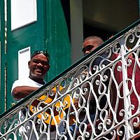 Central America, Cuba, Havana. Cuban playing guitar on balcony in Old Havana.