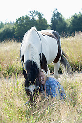 Mid adult woman stroking her horse on meadow and smiling, Bavaria, Germany