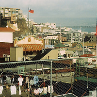 1. When was this photo taken?<br /> <br /> 2007 (?)<br /> <br /> 2. Where was this photo taken? <br /> <br /> Chinatown, San Francisco, CA<br /> <br /> 3. Who took this photo?<br /> <br /> I did - Nicole Barens<br /> <br /> 4. What are we looking at here?<br /> <br /> This is a view of rooftops in Chinatown with the San Francisco Bay in the distance. You'll notice two Taiwanese flags and a building dated 1920 with a Chinese style pagoda roof and painted balcony typical of the time.<br /> <br /> 5. How does this old photo make you feel?<br /> <br /> It makes me a little nostalgic for City College's old satellite campuses. They were very run down but full of character. We now have a big, modern multistory building, which definitely facilitates teaching and the learning process, but sometimes I miss the cozy chaos of the old buildings.<br /> <br /> 6. Is this what you expected to see?<br /> <br /> No -- I'd completely forgotten I'd taken these photos.<br /> <br /> 7. What kind of memories does this photo bring back?<br /> <br /> It makes me remember teaching ESL to packed classes of primarily Chinese students. There was often a sense of barely managed chaos in these classes for reasons I've never quite understood, I could never get a good 50% of the large classes to follow directions. Despite, or maybe because of this, it brings a smile to my face because we usually ended up having fun and I managed to teach something despite the seeming disorder. No matter how many times I taught there and because I am not Chinese, I still always felt a small charge of excitement when entering Chinatown as an instructor -- that small sense of wonder that accompanies traveling to a new culture.<br /> <br /> 8. How do you think others will respond to this photo?<br /> <br /> I think perhaps it will inspire some curiosity, where is this? It might also provide that sense of an insider's view that one cannot get from the street in a dense city. It is only when you enter one of the building