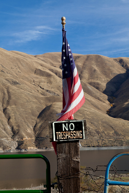 American Flag and No Trespassing sign share fence post on the Snake River in Hells Canyon. Licensing and Open Edition Prints.