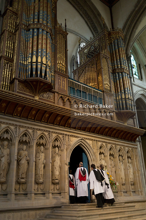 Choristers pass beneath the organ in Rochester cathedral, on 22nd July, in Rochester, England