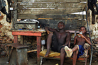GHANA,Accra,Jamestown, 2007. Taking a break from their tire repair business, workers relax in the afternoon heat.