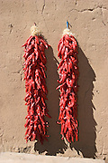Pair of red chili ristras hang on adobe wall.