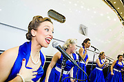 The Pocket Belles sing at the opening of the Sunseeker stand. The London Boat Show opens at the Excel Centre, Docklands, London, UK 04 January 2014. Guy Bell, 07771 786236, guy@gbphotos.com