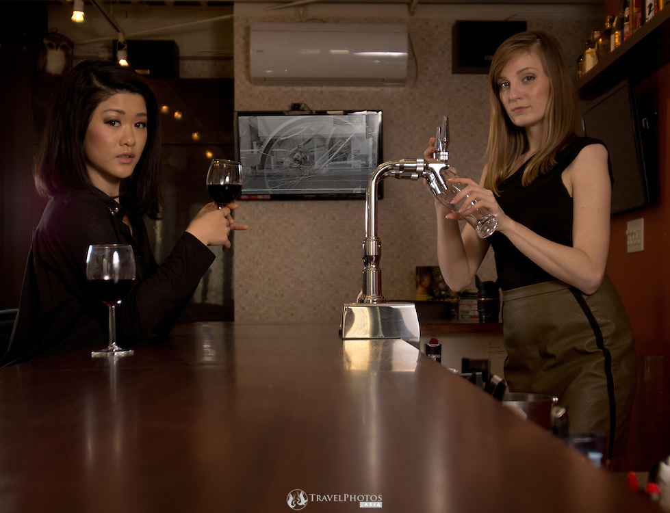 A young Japanese woman customer being served at a bar in Osaka by a Caucasian woman.
