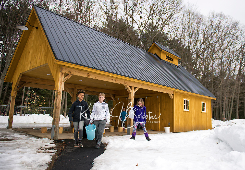 Lucas Diaz, Tucker Crawford, Kaitlin Herbert and Maria Pena head out with buckets to collect sap at Gilford Elementary School's new sap house.  (Karen Bobotas/for the Laconia Daily Sun)