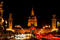 Blurred traffic, Pont Alexandre III (bridge) across the Seine River with Hotel des Invalides behind. The bridge is the most ornate in the city and features art nouveau lamps, cherubs, nymphs and on the two large gilded sculptures at the end, winged horses. Paris, France.