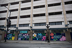 People walk past closed businesses with a mural that says 'Come Together, Stay Apart' on the boarded up windows, in downtown Vancouver, BC, Canada on Sunday, April 19, 2020. TPhoto by Darryl Dyck/CP/ABACAPRESS.COM