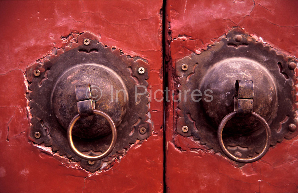 The weathered door and pulls of a courtyard house's entrance, Beijing city, China.
