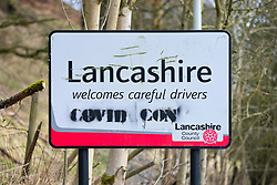 """© Licensed to London News Pictures . 19/03/2021. Cornholme , UK . A sign defaced with the words """" COVID CON """" is seen on the border between West Yorkshire and Lancashire The sign reads """" Lancashire welcomes careful drivers """" . Exploring a year of experiences , lessons and consequences of Coronavirus in the NW of England . Photo credit : Joel Goodman/LNP"""