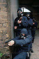 City of London Tactical Firearms officers seen with gas masks and weapons during a training exercise in London in 1991. Photograph by Terry Fincher