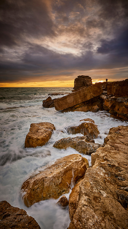 A romantic couple looking at the Pulpit Rock with a stormy sky sunset behind them and ocean waves breaking over the rocks in the foreground.