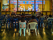 "30 JANUARY 2016 - NONTHABURI, NONTHABURI, THAILAND: The audience watches a ""likay"" performance at Wat Bua Khwan in Nonthaburi, north of Bangkok. Likay is a form of popular folk theatre that includes exposition, singing and dancing in Thailand. It uses a combination of extravagant costumes and minimally equipped stages. Intentionally vague storylines means performances rely on actors' skills of improvisation. Like better the known Chinese Opera, which it resembles, Likay is performed mostly at temple fairs and privately sponsored events, especially in rural areas. Likay operas are televised and there is a market for bootleg likay videos and live performance of likay is becoming more rare.     PHOTO BY JACK KURTZ"