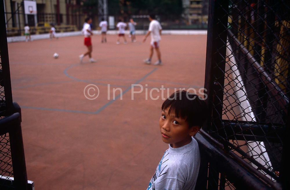 A portrait of a worried-looking young boy as he watches a game of basketball with older boys at a local sportsground, on 10th August 1994, in Macau, China. The Macau Special Administrative Region is one of the two special administrative regions of the Peoples Republic of China PRC, along with Hong Kong. Administered by Portugal until 1999, it was the oldest European colony in China, dating back to the 16th century. The administrative power over Macau was transferred to the Peoples Republic of China PRC in 1999, 2 years after Hong Kongs own handover.