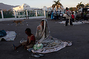 A woman and her son wakes up after spending the night on the street in front of the collapsed National Palace in Port-au-Prince, Saturday, Jan. 30, 2010. A 7.0-magnitude earthquake hit Haiti on Jan. 12, killing and injuring thousands. (AP Photo/Rodrigo Abd)