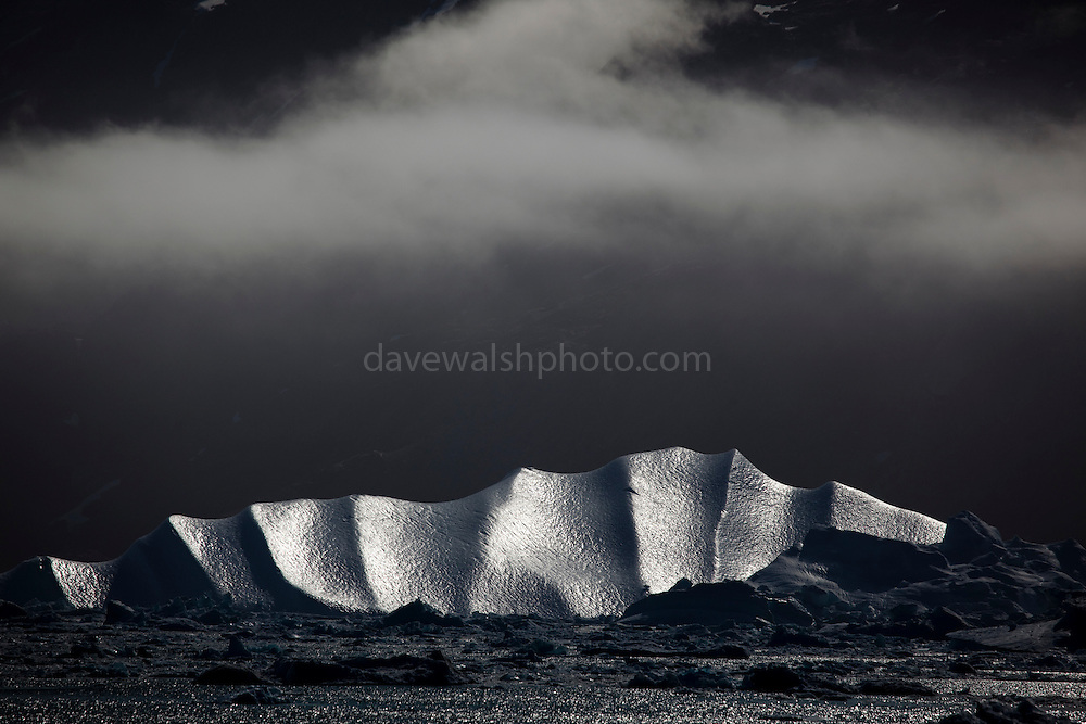 """Sleeping Dragon, Kangerdlugssuaq Fjord, East Greenland. <br /> <br /> Limited edition Giclée Prints available - contact me for more details.<br /> <br /> <br />  This iceberg is calved from Kangerdlussuaq glacier, the largest glacier on the east coast of Greenland's ice sheet and probably the world's fastest moving glacier. Kangerdlugssuaq tripled its speed between 2004 and 2005, and is now rapidly moving mass out of the middle of Greenland's ice sheet, in the form of icebergs. This has urgent implications for both the mass balance of the Greenland ice sheet, and for the rate of sea level rise globally.<br /> Taken from the deck of the Greenpeace ship Arctic Sunrise, during a 2009 expedition to investigate the effects of climate change in the Arctic. <br /> <br /> This mage can be licensed via Millennium Images. Contact me for more details, or email mail@milim.com For prints, contact me, or click """"add to cart"""" to some standard print options."""