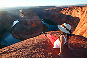 female hiker with hat, relaxes at Horseshoe Bend Colorado River Arizona USA