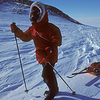 With gusts in his face, South Pole Ski Expedition member J.K. Bajaj of India (MR) negotiates wind-sculpted sastrugi snow by a small nunatak at 80 degrees south latitude in Antarctica.