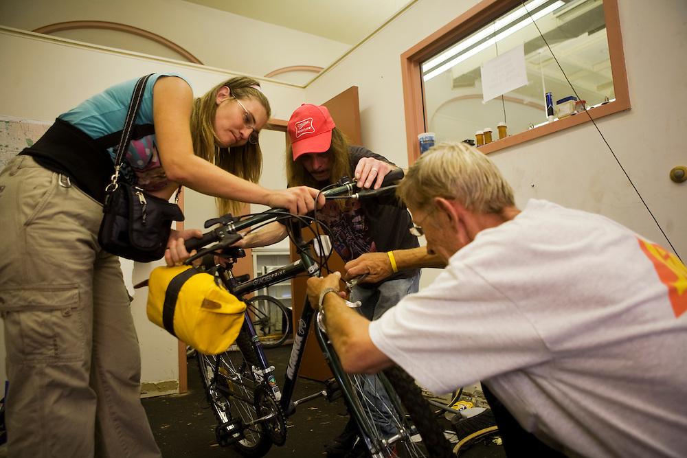 Edward Cenefelt works on a brake line while Lisa Bray and James Laes hold the bike.
