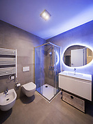 Modern marble bathroom with backlit mirror. Relaxing light. Nobody inside