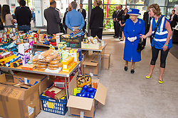 Queen Elizabeth II is shown donations of aid by Executive Director of Kensington and Chelsea Council Sue Harris during a visit to the Westway Sports Centre, London, which is providing temporary shelter for those who have been made homeless in the Grenfell Tower disaster.