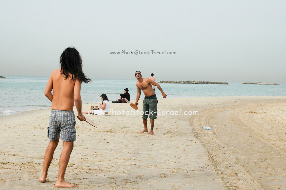 Israel, Tel Aviv, Two young men playing with a bat and ball AKA Matkot on the beach.