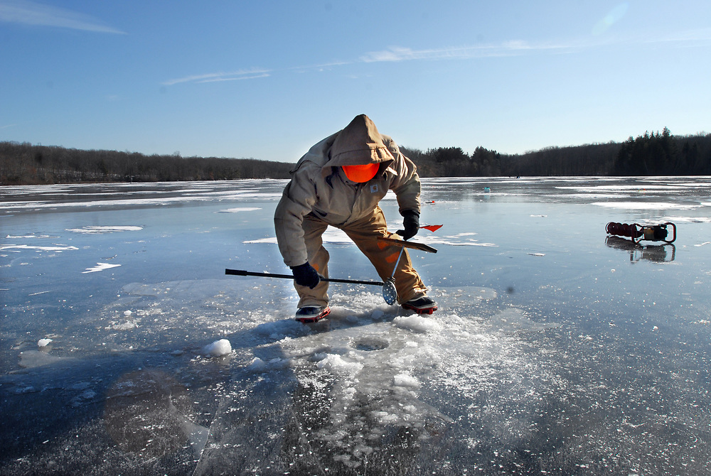 1/31/10 Fish<br /> ML0598<br /> Ray Ledger of Killingworth cleaned newly-formed ice from around the area of one of his tip-ups on Messerschmidt Pond in Westbrook. Ledger was fishing for bass and pickerel. Photo by Mara Lavitt