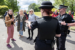 """© Licensed to London News Pictures. 16/05/2020. Manchester, UK. A woman shouts abusive comments about Jimmy Saville , Jeffrey Epstein , Aldus Huxley and George Orwell at police , as officers request she maintains social distancing from them , at the demo . An anti-lockdown, """"mass gathering"""" demonstration is held in Platt Fields Park in protest at government measures to control the spread of Covid-19. A group calling itself the UK Freedom Movement has organised a series of demonstrations across the UK. Photo credit: Joel Goodman/LNP"""