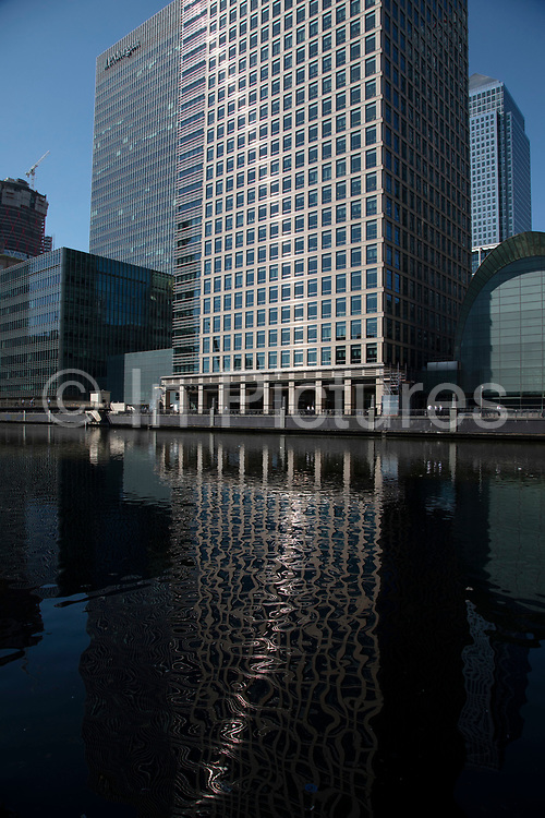 Reflections of towers on South Dock in Canary Wharf financial district in London, England, United Kingdom. Canary Wharf is a financial area which is still growing as construction of new skyscrapers continues.
