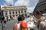 "Tourists consult a map opposite L'Opera - known as the Palais Garnier - in Paris, France. We look over the shoulders of the two tourists who are pointing and looking at the street plan of the French capital, on a summer's day. The Palais Garnier is a 1,979-seat opera house, which was built from 1861 to 1875 for the Paris Opera. It was originally called the Salle des Capucines because of its location on the Boulevard des Capucines in the 9th arrondissement of Paris. The Palais Garnier is ""probably the most famous opera house in the world, a symbol of Paris."