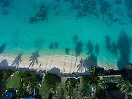 An aerial photograph of the late afternoon sun casting palm treeshadows onto Lanikai Beach, Oahu, Hawaii