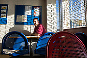 A prisoner sitting in the visit hall waiting for his family to arrive. HMP/YOI Portland, Dorset. A resettlement prison with a capacity for 530 prisoners. Dorset, United Kingdom.